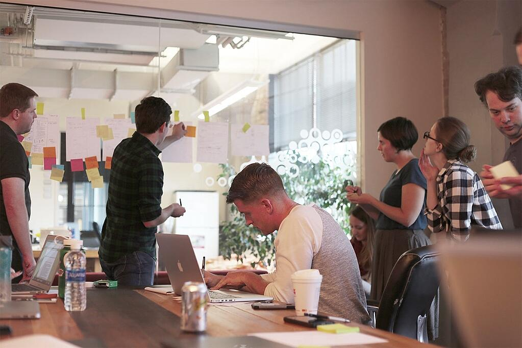 Group of six people collaborating using sticky notes on a window.