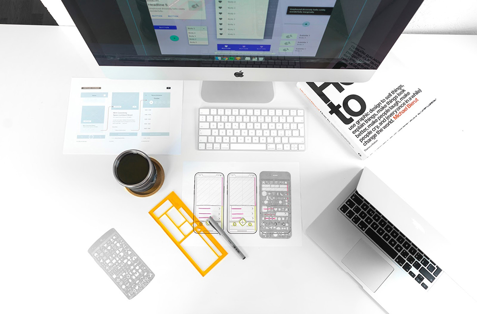 Top down view of a desk with a Mac computer monitor, keyboard, and laptop; a cup of coffee; mobile app wireframes; a book and pen.