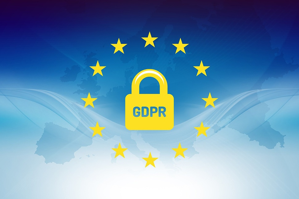 """Blue faded map of Europe in the background. 12 yellow stars circling a yellow padlock with the letters """"GDPR"""" in the foreground."""