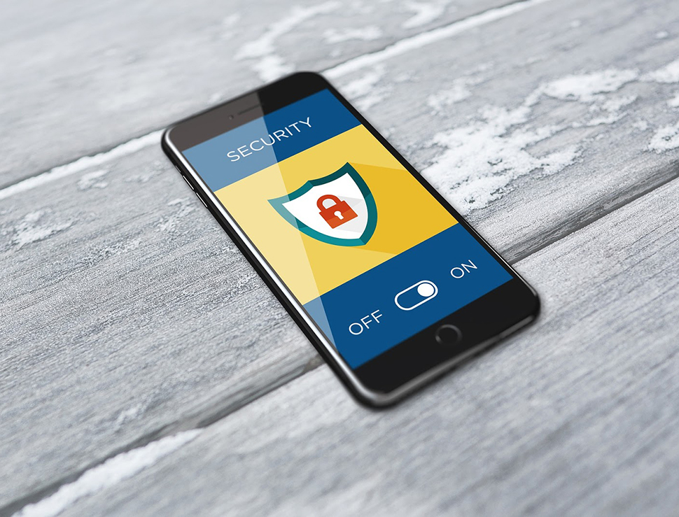 "Smartphone on a grey wooden background with the screen showing a padlock within a shield and the words ""Security"" above and ""Off"" ""On"" below"