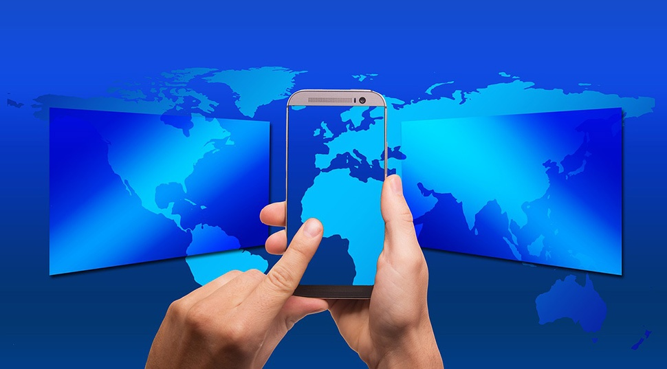 Flat map of the world in different shades of blue with someone holding a smartphone in front of it.