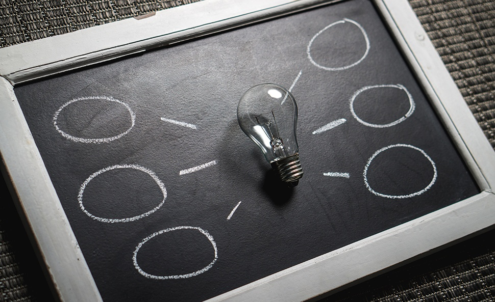 Light bulb on a small blackboard surrounded by idea circles drawn in chalk.