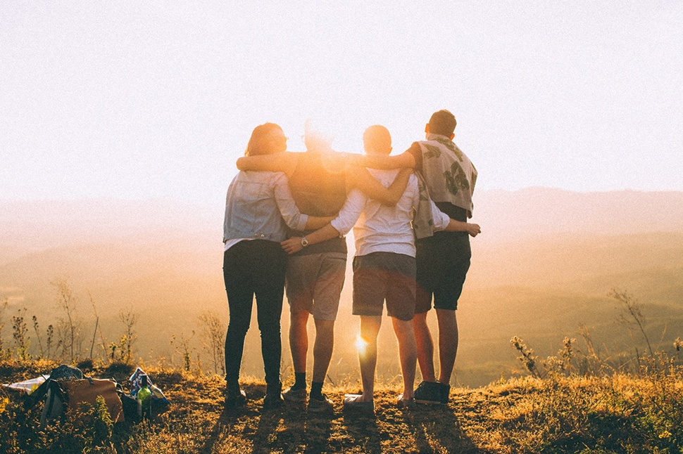 Four people with their backs to the camera overlooking a hillside on a bright day.