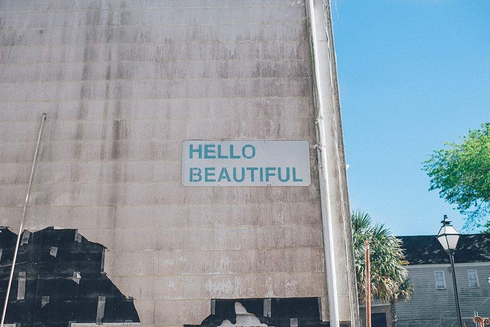 """Large gray wall outside with the text """"HELLO BEAUTIFUL"""" spelled out on it."""