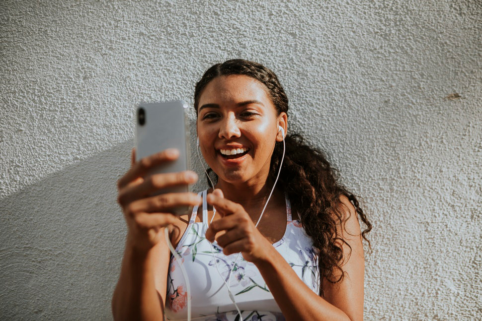 Woman wearing fitness outfit and ear buds, smiling while using her smartphone