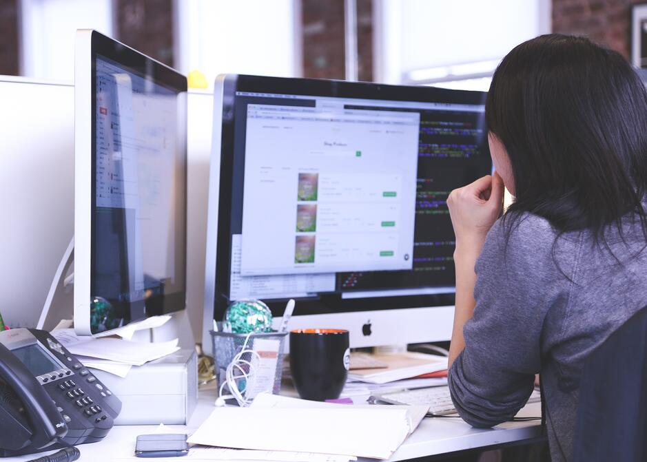 Women_looking_at_two_computer_screens_on_desk.jpg