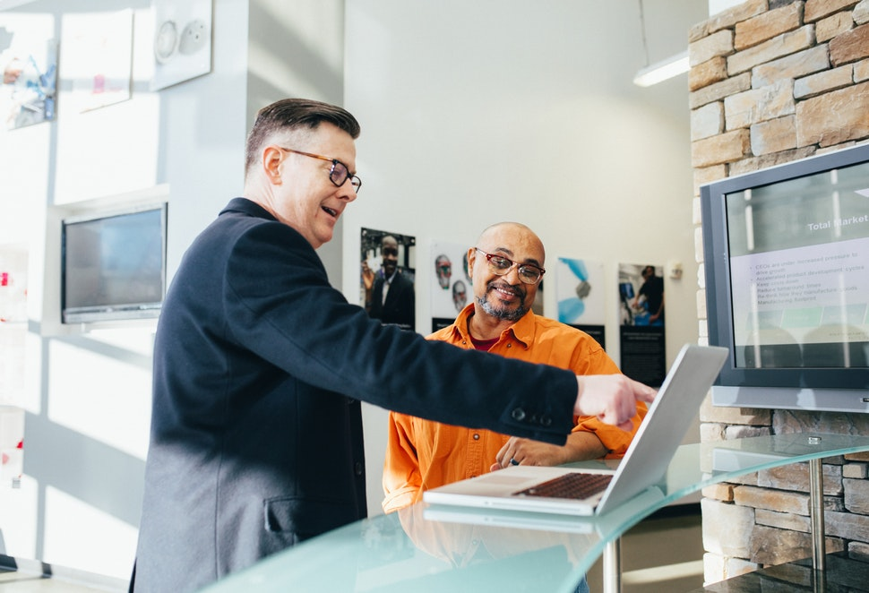 Two smiling men looking at a laptop, one of them pointing at the screen