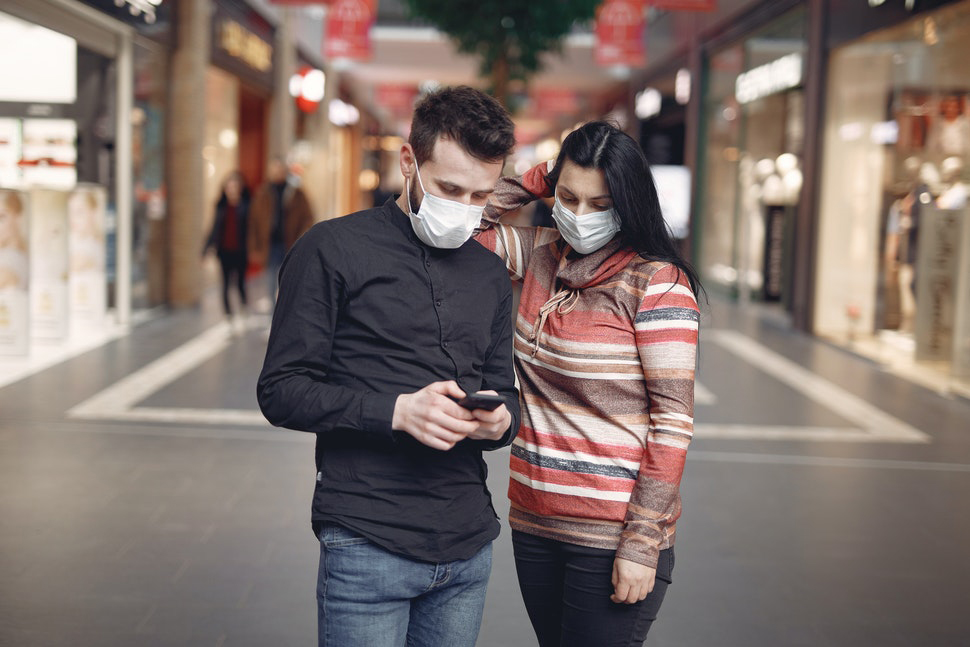 Two shoppers wearing face masks looking at a mobile device