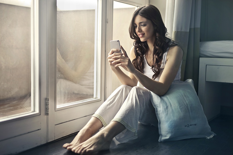 Woman in pajamas siting by glass door holding and looking at smartphone.