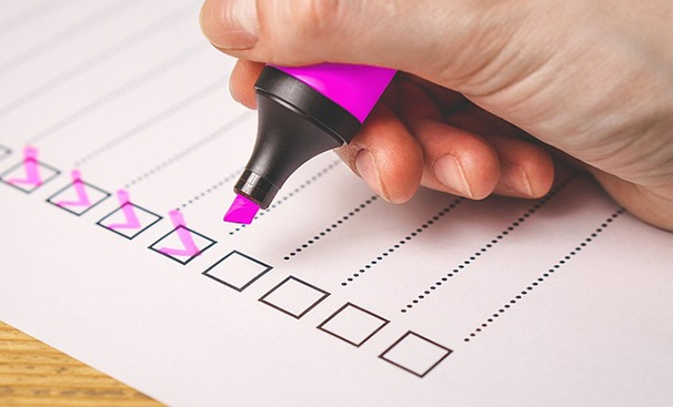 A hand holding a pink highlighter over a piece of paper with pink check marks in some of the checkboxes.