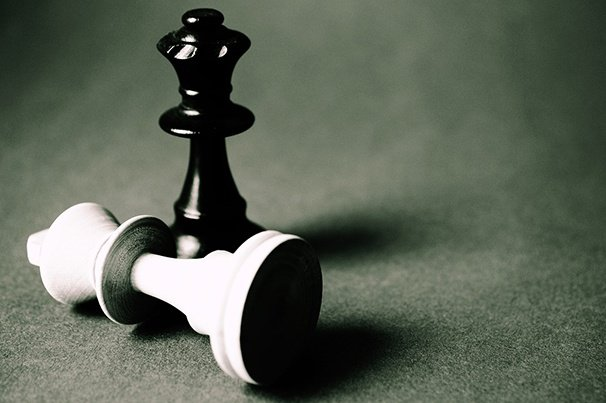A white chess piece down and a black chess piece behind it standing up, representing checkmate.