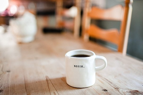 "Coffee mug with the word ""Begin"" sitting on a wooden table with wooden chairs in the background"