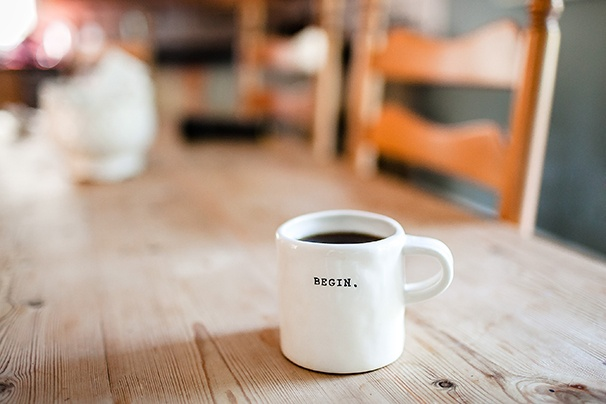 """Coffee mug with the word """"Begin"""" sitting on a wooden table with wooden chairs in the background"""