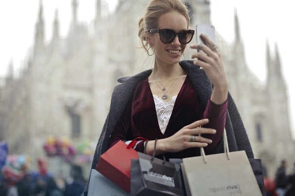 Woman wearing sunglasses looking at her smartphone with shopping bags over her arms and a city view in the background