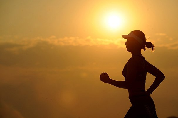 Woman in exercise clothes running with bright sunlight in the background.
