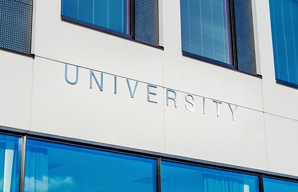 "Close up of a building with a sign that reads ""University."""