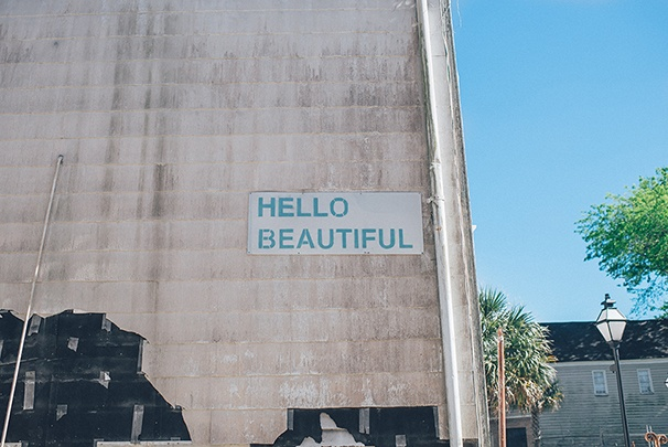 "Large gray wall outside with the text ""HELLO BEAUTIFUL"" spelled out on it."