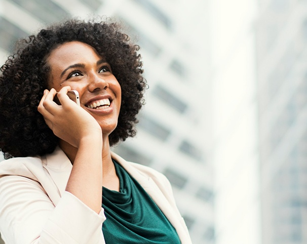 Woman in business attire smiling and holding a cell phone to her ear.
