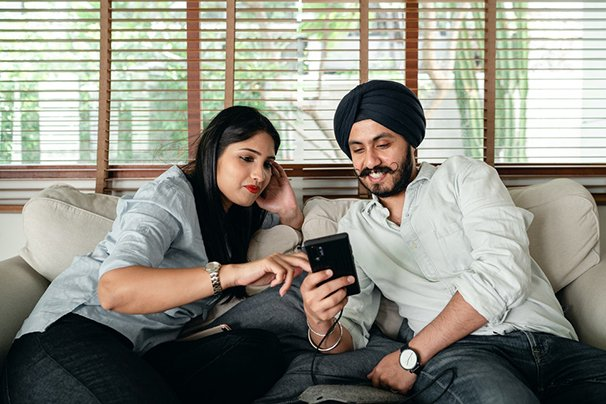 A couple at home looking at a smartphone